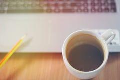 Kawowy kubek na biurku Z notebookiem, ołówek, drewniany stołowy wierzchołek z jaskrawym ranku światłem słonecznym obraz stock
