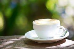 Kawowy kubek na drewnianym stole z zielonym bokeh tłem fotografia stock
