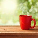Kawowy kubek nad ogrodowym bokeh Zdjęcie Royalty Free