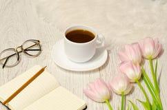 Kawowy kubek, notatnik z piórem i menchia tulipany na stole, Zdjęcia Stock