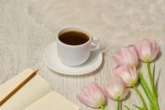 Kawowy kubek, notatnik z pustymi stronami i różowi tulipany na stole, Fotografia Stock