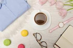 Kawowy kubek, okulary przeciwsłoneczni, zegarki, notatnik i menchia tulipany na stole, Pracujący pojęcie Obraz Stock
