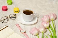 Kawowy kubek, okulary przeciwsłoneczni, zegarki, notatnik i menchia tulipany na stole, Pracujący pojęcie Odgórny widok Fotografia Stock