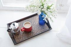 Kawowy kubek, kawowy producent z białych kwiatów bukietem na tacy Fotografia Stock