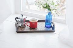 Kawowy kubek, kawowy producent z wazą kwiaty na drewnianej tacy na windowsill Zdjęcia Royalty Free