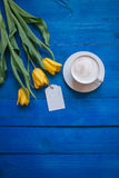 Kawowy kubek z żółtymi tulipanowymi kwiatami Zdjęcia Royalty Free