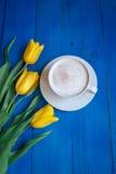 Kawowy kubek z żółtymi tulipanowymi kwiatami Obrazy Stock