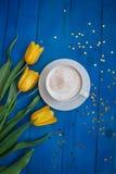 Kawowy kubek z żółtymi tulipanowymi kwiatami Fotografia Stock