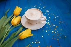 Kawowy kubek z żółtymi tulipanowymi kwiatami Obraz Stock
