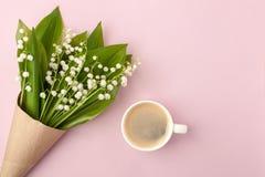 Kawowy kubek z bukietem kwiat leluja dolin menchii pastelowy tło, piękny śniadanie, rocznik romantyczna karta, odgórny widok zdjęcie royalty free