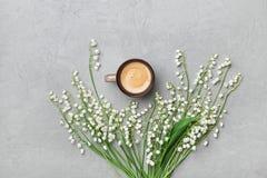 Kawowy kubek z bukietem kwiat leluja dolina na kamienia stole od above w mieszkanie nieatutowym i minimalistic stylu fotografia royalty free