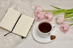 Kawowy kubek z cukierkiem, notatnikiem z pustymi stronami i różowymi tulipanami na stole, Obrazy Royalty Free