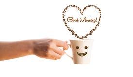 Kawowy kubek z kawowych fasoli kształtującym sercem z dnia dobrego znakiem Obrazy Stock