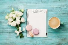 Kawowy kubek z macaron, białymi kwiatami i notatnikiem z robić liście na błękitnym wieśniaka stole od above, Piękny śniadaniowy m Zdjęcie Royalty Free
