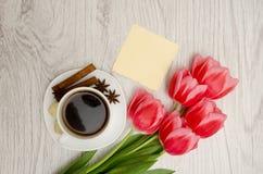 Kawowy kubek z pikantność, czysta notatka, różowi tulipany na drewnianym plecy Obraz Royalty Free