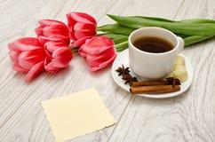Kawowy kubek z pikantność, czysta notatka, różowi tulipany na drewnianym tle, wiosny śniadanie Zdjęcia Royalty Free