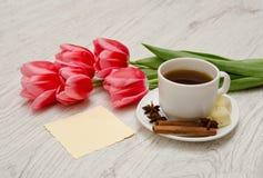 Kawowy kubek z pikantność, czysta notatka, różowi tulipany na drewnianym tle, wiosny śniadanie Zdjęcia Stock