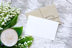 Kawowy kubek z pustym kartka z pozdrowieniami i kwiatów bukietem leluja dolina Zdjęcia Royalty Free