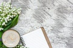 Kawowy kubek z pustym notatnika i kwiatów bukietem leluja dolina Zdjęcia Stock