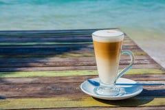 Kawowy latte na drewnianym stole z dennym tłem Obrazy Stock