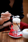 Kawowy latte w szklanej filiżance z rękojeścią, wysoka piana Stać na czerwonej pielusze Ręki z łyżką Zdjęcia Stock