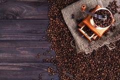 Kawowy młyn na ciemnym drewnianym tle, odgórny widok Obrazy Stock
