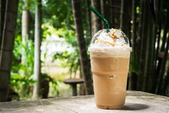 Kawowy miesza wewnątrz plastikową filiżankę Słuzyć z batożącym kremowym polewy i cukierki syropem zdjęcie royalty free