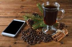 Kawowy napój i smartphone z Bożenarodzeniową dekoracją na wo, Zdjęcie Royalty Free