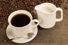 Kawowy pojęcie: Filiżanka czarna kawa, kawowe fasole i kremowy dzbanek na starym drewnianym stole, Zdjęcia Royalty Free