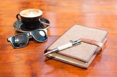 Kawowy słońc szkieł pióro i agenda na drewnianym stole Fotografia Royalty Free