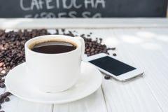 Kawowy tło z fasolami i białą filiżanką kosmos kopii fotografia stock