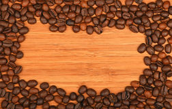 Kawowych fasoli granicy rama nad bambusowym drewnianym tłem Obrazy Stock