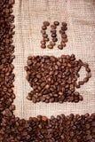 Kawowych fasoli kubek na workowego płótna tle Obrazy Stock