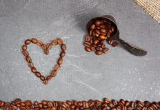 Kawowych fasoli luźny uczciwy handel z łyżką i serce przy kuchennym worktop tłem obraz stock