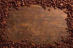 Kawowych fasoli rama na drewnianym stole Zdjęcie Royalty Free
