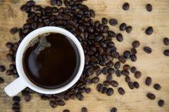 Kawowych fasoli tło na drewnianych, Świeżych kawowych fasolach z filiżanką na drewnianym tle, Pije ustalonego tło Obrazy Stock
