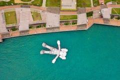 KAWS伴侣,漂浮在水的巨型雕塑鸟瞰图  图在维多利亚港口,香港 中华民国 免版税库存图片