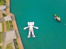 KAWS伴侣,漂浮在水的巨型雕塑鸟瞰图  图在维多利亚港口,香港 中华民国 库存图片