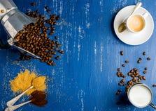 Kawy espresso filiżanka, śmietanka, arabika fasole w moka puszkuje, brown cukier i ziemi kawa na drewniany błękit malującym tle Fotografia Royalty Free