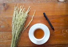 Kawy espresso kawa z piórem i ryż na drewnianym stole obrazy stock