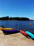 Kayak #2. Kayaks resting along shore of lake, with lone kayaker in distance Stock Images