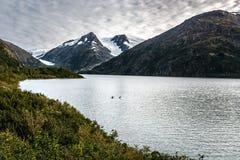 Kayak In Alaska. Kayak scene in Alaska with mountains in background royalty free stock photo
