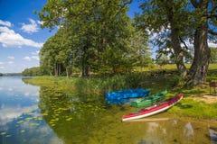 Kayak and boats on the lake shore Stock Photos