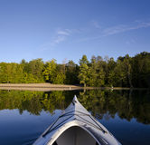 Kayak on Calm Lake. Composite of single kayak resting on calm Charleston Lake facing the beach area with the late day light on the shoreline Royalty Free Stock Photos