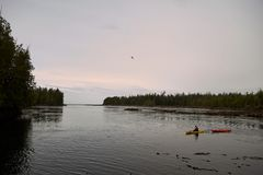 Kayak de navigation de personne sur la rivière au coucher du soleil Images stock
