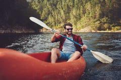 Kayak del giovane su un lago fotografia stock