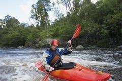Kayak dell'uomo in fiume fotografie stock