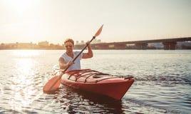 Kayak dell'uomo sul tramonto fotografia stock