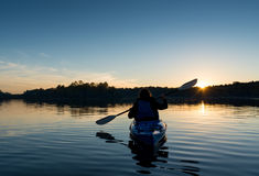 Kayak della donna al tramonto immagine stock