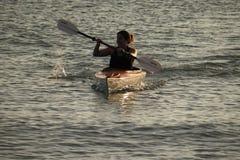 Kayak della giovane donna fuori dall'isola di Captiva al tramonto fotografie stock